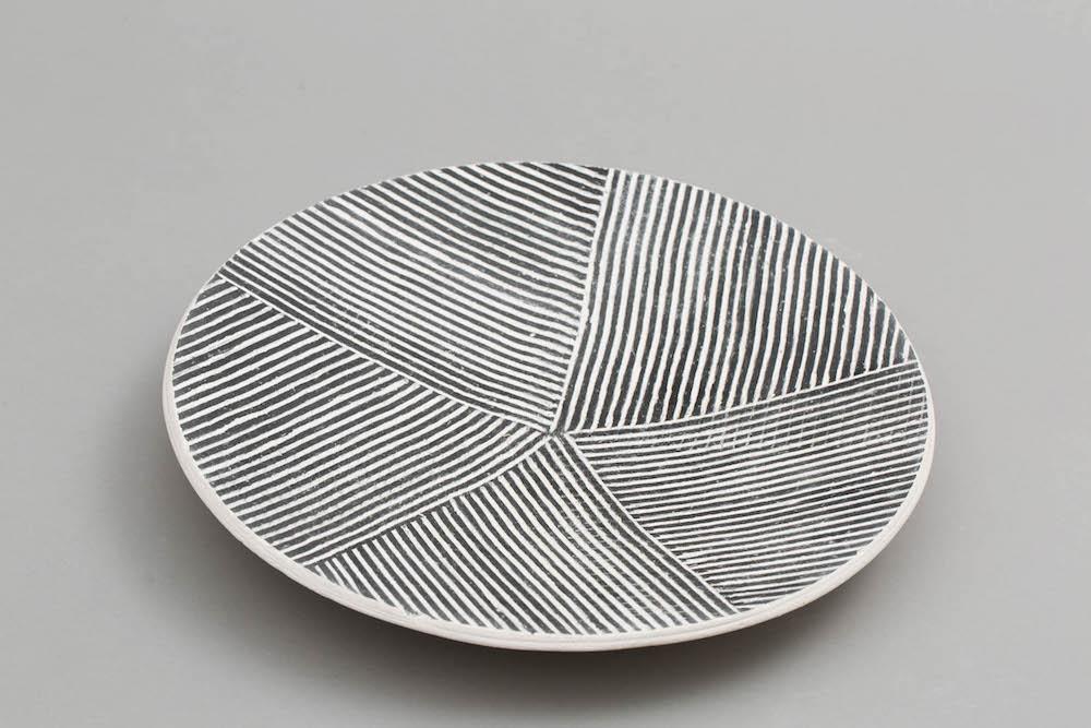 Assiette en porcelaine tournée à décor à l'engobe inspiré des mortiers suribachi.